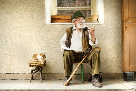 village man: Old man reading the newspaper in front of his house