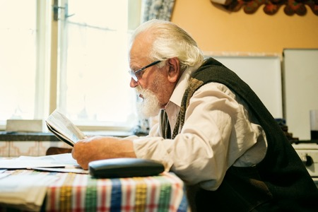 adult 80s: Old man reading the newspaper at home Stock Photo