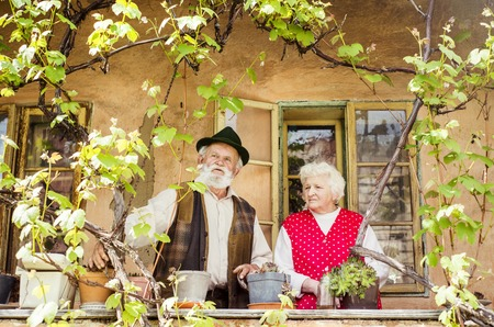 Outdoor portrait of old couple standing by their village house photo