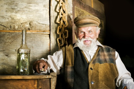 adult 80s: Portrait of old farmer with beard and hat holding a bottle of herbal spirit