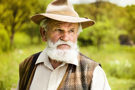 Portrait of old farmer with beard and hat in his backyard photo