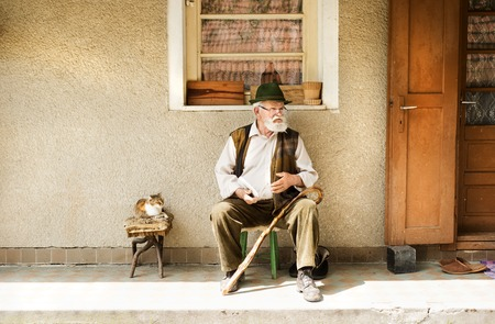 Old man reading the newspaper in front of his house photo