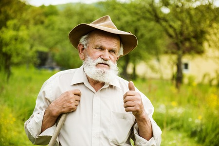 Old farmer with beard working with rake in garden Stock Photo