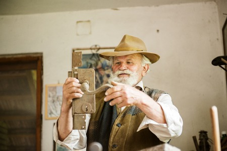 gaffer: Old farmer with beard and hat holding horseshoe Stock Photo