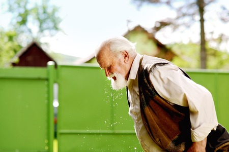 Old farmer is washing his face with water from bucket photo