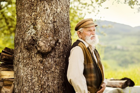 agriculturalist: Old farmer with beard is walking in meadow