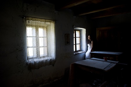 Lovely and happy brunette bride posing in old house