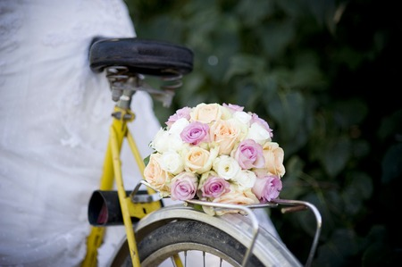 Close-up of bride in white wedding dress on retro bicycle photo