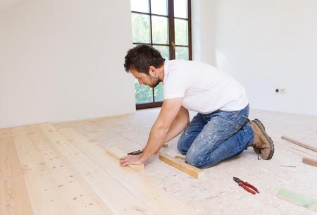 Handyman installing wooden floor in new house Imagens