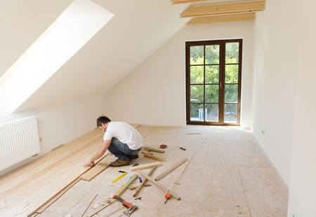 Handyman installing wooden floor in new house Stock Photo