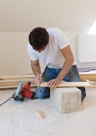 installing: Handyman installing wooden floor in new house Stock Photo