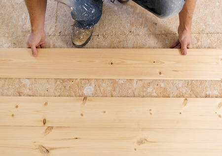 laminate: Handyman installing wooden floor in new house Stock Photo