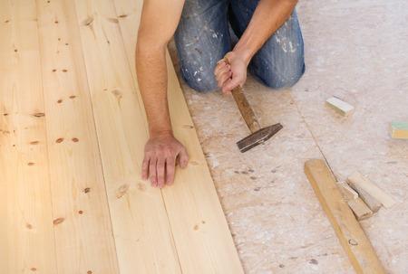 wooden floor: Handyman installing wooden floor in new house Stock Photo