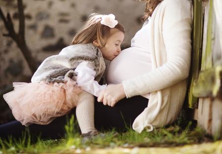 bacio: Ritratto di bambina baciare il ventre della madre incinta s Archivio Fotografico