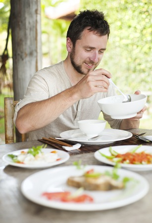 Man enjoying a meal with chopsticks in vietnamese restaurant photo
