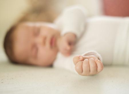 Newborn baby girl is sleeping on the bed photo