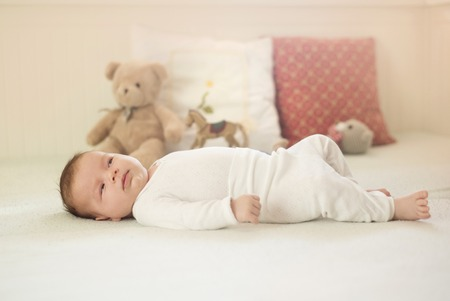 Newborn baby girl is laying down on the bed photo