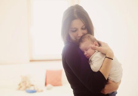 嬰兒: 年輕的母親抱著她的小寶寶 版權商用圖片