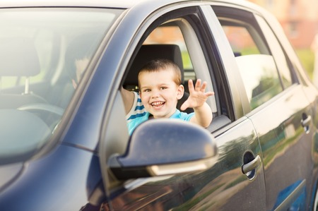 Young father with his little son driving car together photo