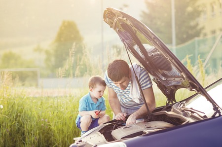 auto repair: Young father with his little son repairing car Stock Photo