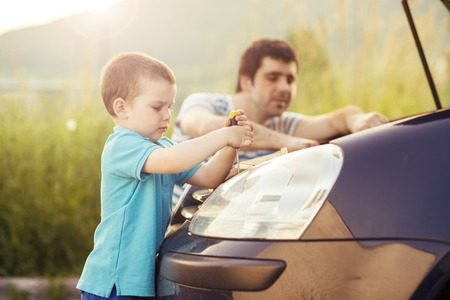 Young father with his little son repairing car photo