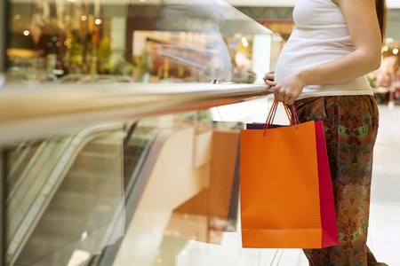 Unrecognizable pregnant woman holding shopping bags in shop store photo