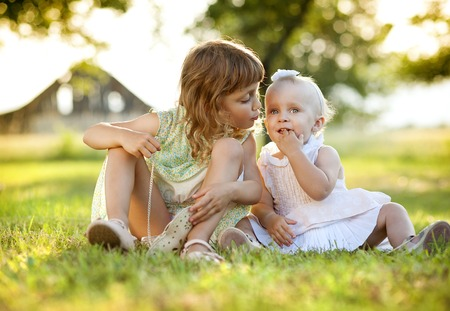 Two cute little sisters laughing and playing in green sunny park photo