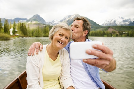pleasure boat: Senior couple on boat with mountains in background taking selfie