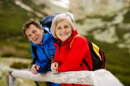 hikers: Senior tourist couple hiking at the beautiful mountains