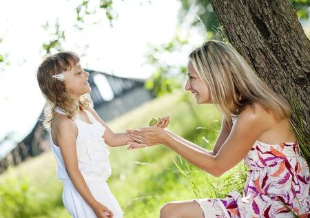 Moeder en kleine dochter tijd doorbrengen togetger in zomertuin