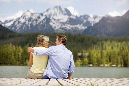 jubilados: Pareja de ancianos sentados en el muelle sobre el lago de montaña con las montañas en el fondo