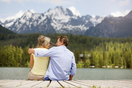 mountain man: Senior couple sitting on pier above the mountain lake with mountains in background