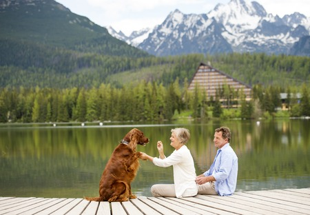 Senior couple with dog sitting on pier above the mountain lake with mountains in background photo