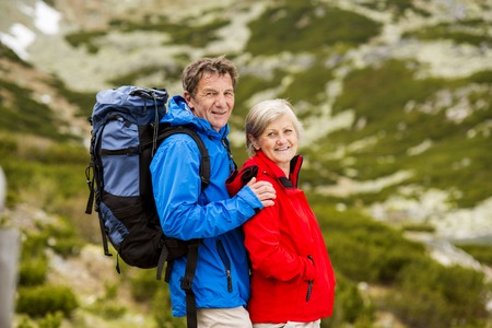 old people walking: Senior tourist couple hiking at the beautiful mountains