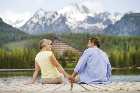 Senior couple sitting on pier above the mountain lake with mountains in background photo
