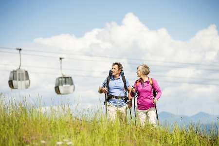 Senior tourist couple hiking at the beautiful mountains, cableway in the background photo