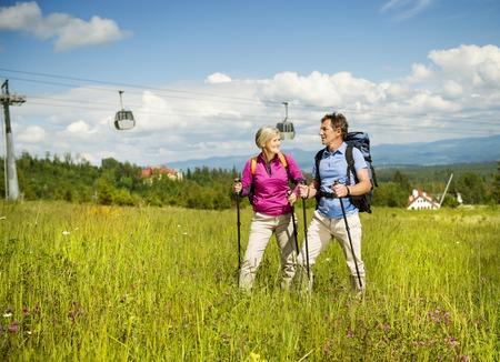 Hogere toerist paar wandelen in de prachtige bergen, kabelbaan op de achtergrond Stockfoto