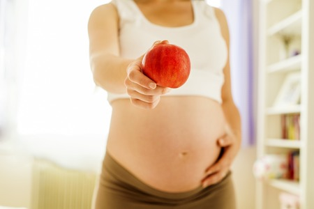Portrait of unrecognizable pregnant woman with an apple in her hand photo