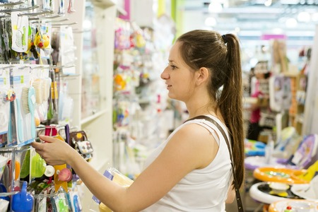 Young pregnant woman choosing baby stuff at baby shop store photo