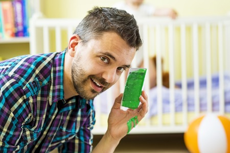 sleazy: Father holding damaged mobile phone and his little daughter in background Stock Photo