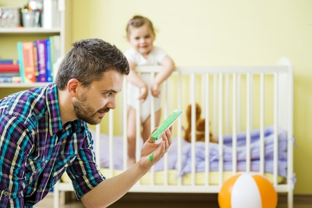 Father holding damaged mobile phone and his little daughter in background Stock Photo