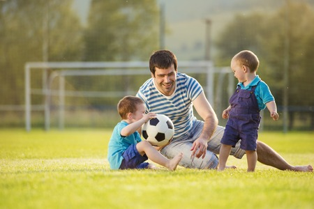 Young father with his little sons playing football on football pitch photo