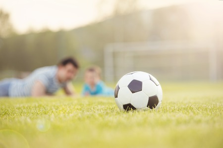 football pitch: Young father with his little son having fun on football pitch Stock Photo