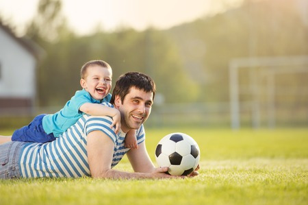 child ball: Young father with his little son having fun on football pitch Stock Photo