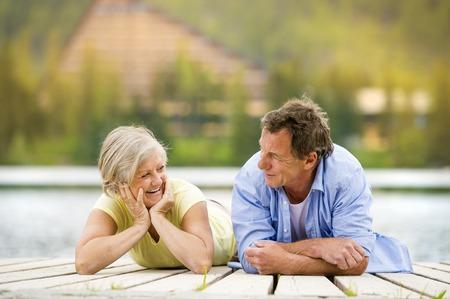 enjoying life: Senior couple lying down and having fun on pier Stock Photo