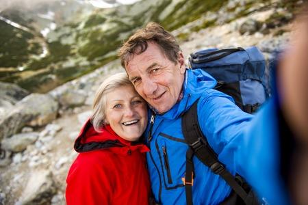 mujeres maduras: Pareja de turistas senior senderismo y tomando selfie en las hermosas montañas