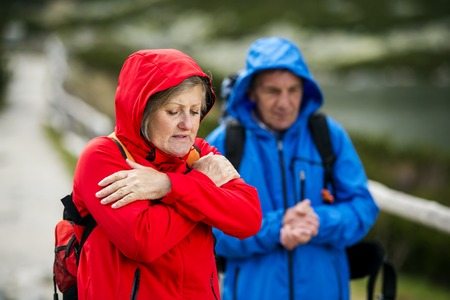 Senior tourist couple hiking at the beautiful mountains in cold weather photo