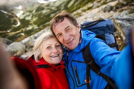 senderismo: Pareja de turistas senior senderismo y tomando selfie en las hermosas monta�as