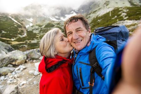 persona de la tercera edad: Pareja de turistas senior senderismo y tomando selfie en las hermosas monta�as