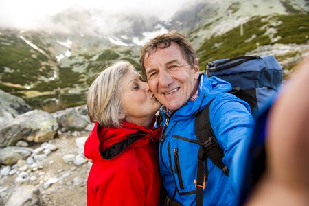 old people: Senior tourist couple hiking and taking selfie at the beautiful mountains